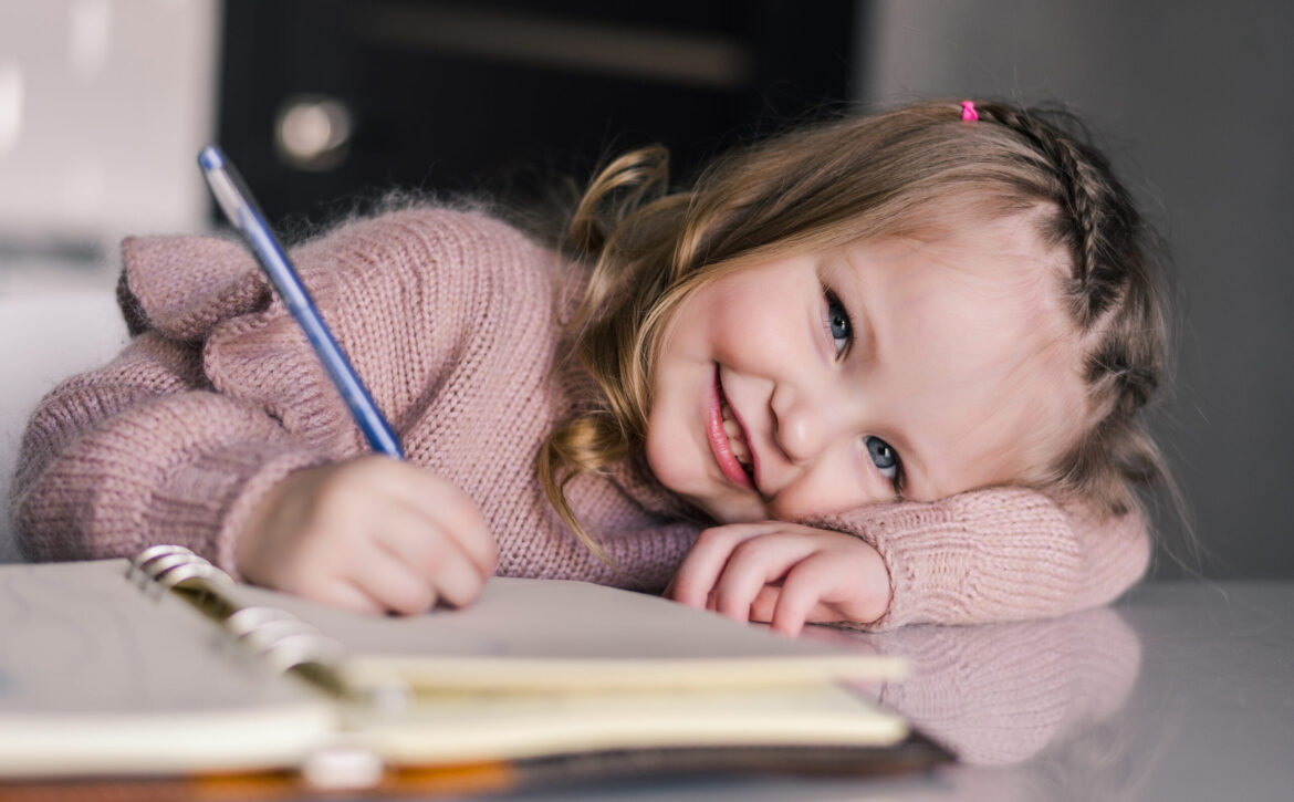 Adorable preschool girl drawing with pen at table. Cute daughter smiling and make kindergarten homework